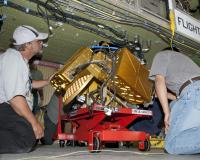 Technicians work on an instrument under a fuselage