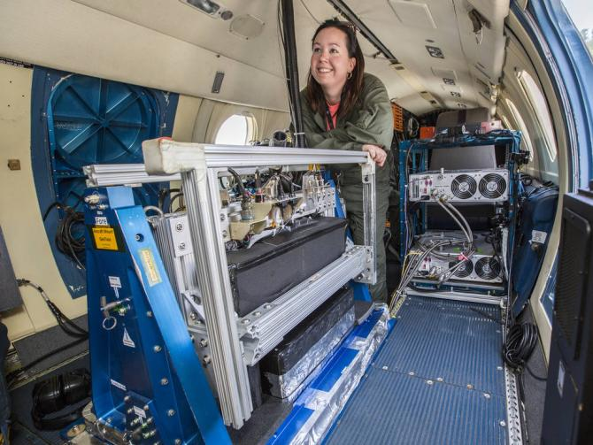 Laura Judd, postdoctoral researcher at NASA Langley, prepares for a LISTOS science flight on the center's HU-25 aircraft. GeoTASO, a remote-sensing instrument that observes reflected sunlight to measure atmospheric trace gases and aerosols over a wide area, is visible in the foreground. Credits: NASA/David C. Bowman