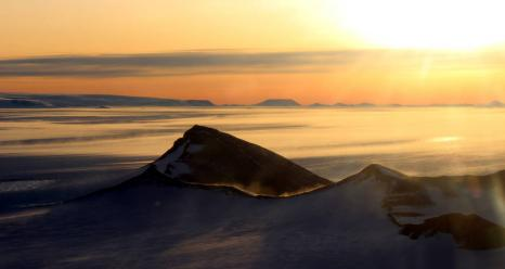 The Shackleton Range in Antarctica at sunset with snow blowing off the ridges, photographed during an Operation IceBridge flight on Oct. 10, 2018. Credits: NASA/Michael Studinger
