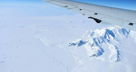 The mountains of northern Alexander Island in the Antarctic Peninsula, passing under the left wing of the DC-8 aircraft carrying Operation IceBridge¹s scientists and instruments on Oct. 14, 2016. Credits: NASA/John Sonntag