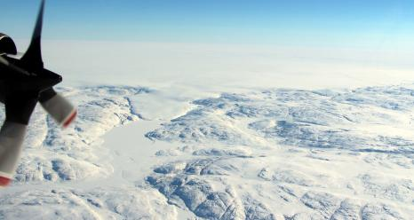 The Hiawatha impact crater is covered by the Greenland Ice Sheet, which flows just beyond the crater rim, forming a semi-circular edge. Part of this edge (top of photo) and a tongue of ice that breaches the crater's rim are shown in this photo taken during a NASA Operation IceBridge flight on April 17. Credits: NASA/John Sonntag