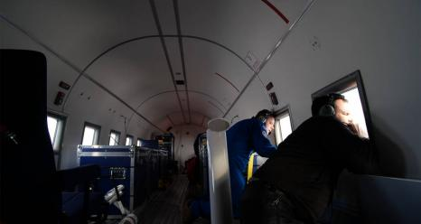 Oceans Melting Greenland Principal Investigator Josh Willis drops a probe during OMG's fall 2018 airborne campaign, then he and flight engineer Glenn Warren watch its descent from the plane windows. Credits: NASA/JPL-Caltech