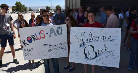 Kyle Kabasares (left), physics major at University of California Merced, and Mariah Heck (right), geophysics and geology major at University of Tulsa hold signs to welcome home the DC-8 crew home from the Korean U.S. Air Quality mission. Credits: NSERC Photo / Jane Peterson
